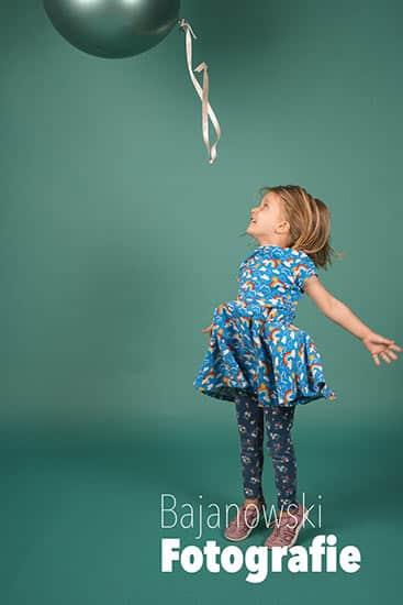 Kitafoto Kind im blauen Kleid mit Ballon